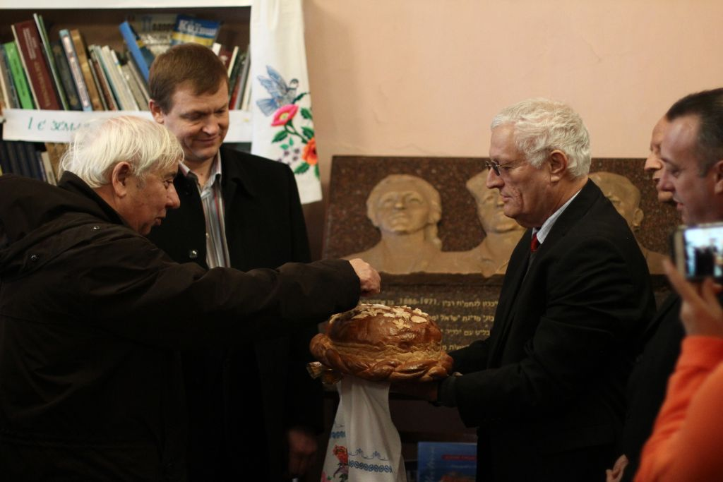 Eitan Haber, Yitzhak Rabin's chief of staff, takes a piece of a traditional Ukranian bread at a ceremony in memory of the prime minister (Courtesy Dmitriy Galin)