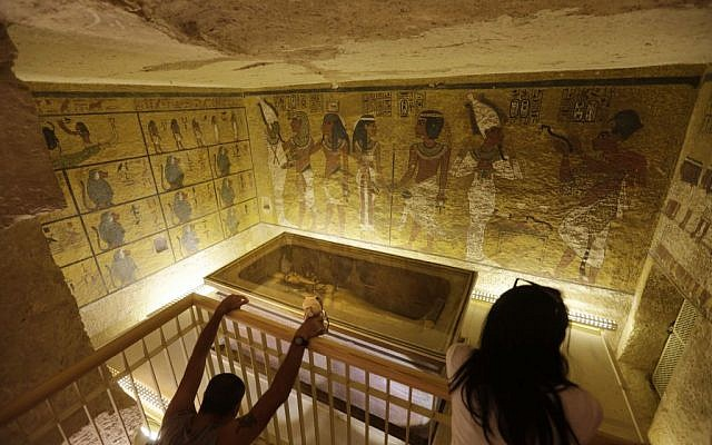 Tourists look at the tomb of King Tut as it is displayed in a glass case at the Valley of the Kings in Luxor, Egypt, November 5, 2015. (AP Photo/Amr Nabil, File)