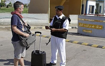 An Egyptian policeman checks a Russian tourist's passport at the main entrance to the Sharm el-Sheikh airport in Egypt on Saturday, Nov. 7, 2015. (AP/Ahmed Abd El-Latif)