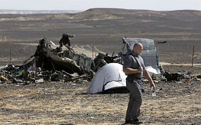 A Russian investigator walks near wreckage November 1, 2015, a day after a passenger jet bound for St. Petersburg, Russia, crashed in Hassana, Egypt. (AP/Amr Nabil, File)
