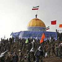 In this Friday, Nov. 20, 2015 photo released by the Tasnim News Agency, members of the Basij, the paramilitary unit of Iran's Revolutionary Guard, gather around a replica of Jerusalem's gold-topped Dome of the Rock mosque as one of them waves an Iranian flag from atop the dome during a military exercise. (AP Photo/Tasnim News Agency, Mahmoud Hosseini)