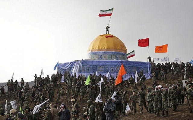 In this Friday, Nov. 20, 2015 photo released by the Tasnim News Agency, members of the Basij, the paramilitary unit of Iran's Revolutionary Guard, gather around a replica of Jerusalem's gold-topped Dome of the Rock mosque as one of them waves an Iranian flag from on top of the dome during a military exercise. (AP Photo/Tasnim News Agency, Mahmoud Hosseini)