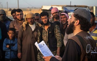 "In this file photo released May 14, 2015 by a militant website, a member of the Islamic State group's vice police known as ""Hisba,"" right, reads a verdict handed down by an Islamic court sentencing many they accused of adultery to lashing, in Raqqa City, Syria. (Photo by AP Photo/Militant Website, File)"