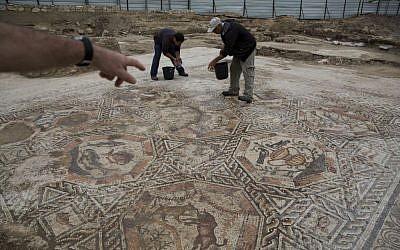 Employees of Israel's antiquities authority work on a 1,700-year-old Roman-era mosaic floor in Lod, Israel, Monday, Nov. 16, 2015 (AP Photo/Ariel Schalit)