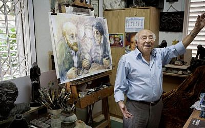 In this photo taken Tuesday, November 10, 2015, artist Itzchak Belfer, who grew up in an orphanage headed by Janusz Korczak, displays a painting of his mentor at his house in Tel Aviv, Israel. (AP Photo/Dan Balilty)