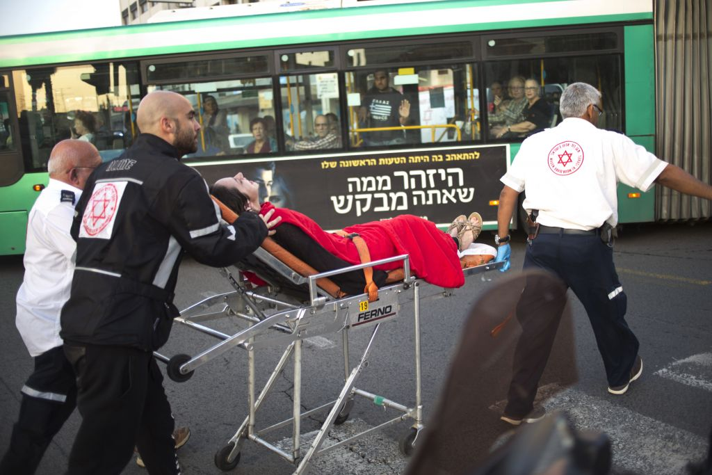 Israeli rescue personal evacuate a woman from a stabbing attack site in Rishon Lezion, Monday, Nov. 2, 2015. (AP Photo/Ariel Schalit)