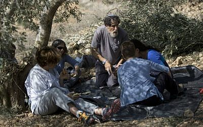 In this Sunday, Nov. 1, 2015 photo, Israeli activist Rabbi Arik Ascherman, center, rests in a Palestinian olive grove during the harvest, in the village of Burin near the West Bank city of Nablus. (AP Photo/Majdi Mohammed)