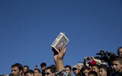 A mourner carries a copy of the Quran during the funeral of Jordanian police Cpt. Anwar Abu Zaid, 28, in his home village of Rimoun, near the city of Jerash, Jordan, November 12, 2015. The police captain opened fire November 9 on instructors at an international police training center in Jordan's capital, killing five people, including two Americans, before being shot dead by security forces. (AP/Nasser Nasser)