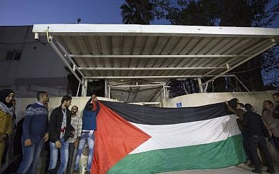 Palestinian Fatah supporters put up a flag while waiting for Gaza's Hamas rulers to hand over the house of late Palestinian President Yasser Arafat to officials from his Fatah party, with the intention of turning it to a museum for the iconic leader, Tuesday, Nov. 10, 2015, Gaza City. (Mahmoud Abbas. (AP/Adel Hana)