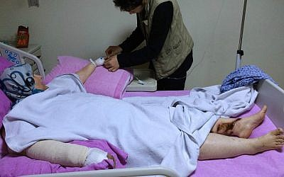 In this picture taken with a mobile phone on Saturday, Oct. 24, 2015, a Syrian boy Abdulhamid Khanfoura, 16, background, helps his wounded mother Zahra Khanfoura, 48, who was burned by a Russian airstrike that hit her house in the central Syrian village of Habeet, as she lies on her hospital bed in the southern city of Kadirli, Turkey (AP /Hussein Malla)