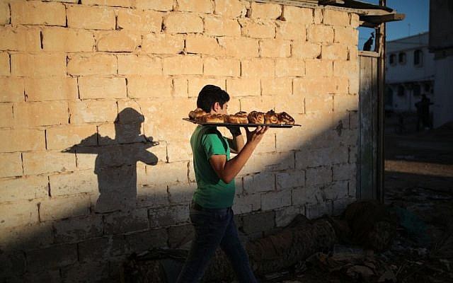 A boy heads home with freshly baked Challah, a special Jewish bread, at the beginning of Shabbath, at Hara Kbira, the main Jewish neighborhood on the Island of Djerba, southern Tunisia, October 29, 2015. (Photo by AP Photo/Mosa'ab Elshamy)