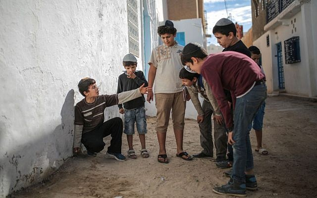 Boys play with marbles outside their school at Hara Kbira, the main Jewish neighborhood in the Island of Djerba, southern Tunisia, October 29, 2015. (Photo by AP Photo/Mosa'ab Elshamy)
