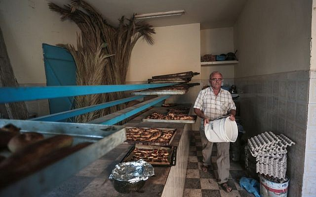 Yofel Sabbagh, 46, walks inside a bakery as he prepares Challah, a special Jewish bread, on the eve of Shabbath, at Hara Kbira, the main Jewish neighborhood on the Island of Djerba, southern Tunisia, October 29, 2015. (Photo by AP Photo/Mosa'ab Elshamy)
