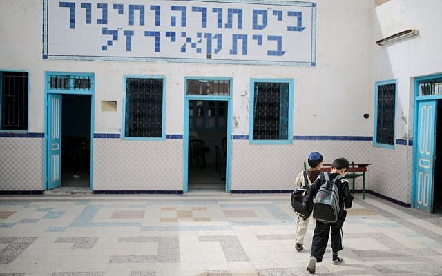 Boys walk inside a Talmudic school at Hara Kbira, the main Jewish neighborhood on the Island of Djerba, southern Tunisia, October 29, 2015. When school lets out, the streets around the ancient synagogue on this Tunisian island fill with rambunctious boys wearing Jewish kippahs and girls in long skirts, shouting to each other in Hebrew, Arabic and French.  (Photo by AP Photo/Mosa'ab Elshamy)