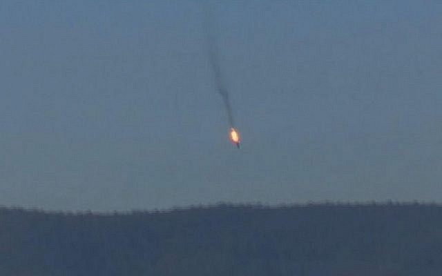 A Russian warplane on fire before crashing on a hill as seen from Hatay province, Tuesday, November 24, 2015. (screen capture: Haberturk TV via AP)