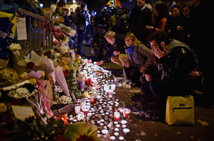People place flowers and candles on the pavement near the scene of the November 13, 2015 Bataclan Theater terrorist attack, on November 14, 2015 in Paris, France. (Photo by Jeff J Mitchell/Getty Images/JTA)