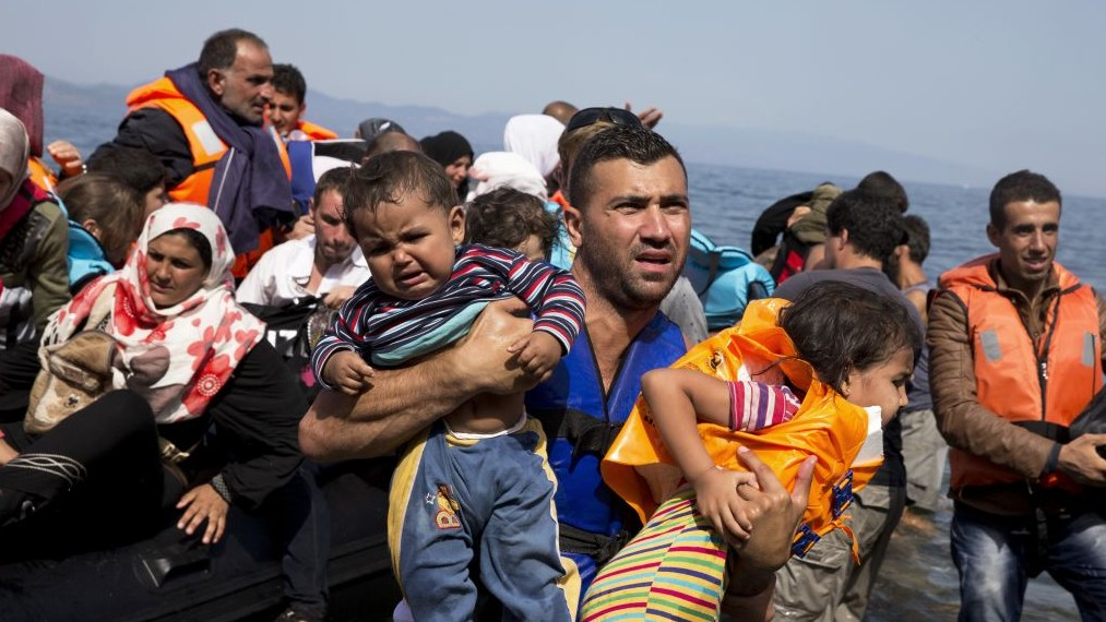 Syrian refugees arrive aboard a dinghy after crossing from Turkey to the island of Lesbos, Greece, on September 10, 2015. (AP/Petros Giannakouris, File)