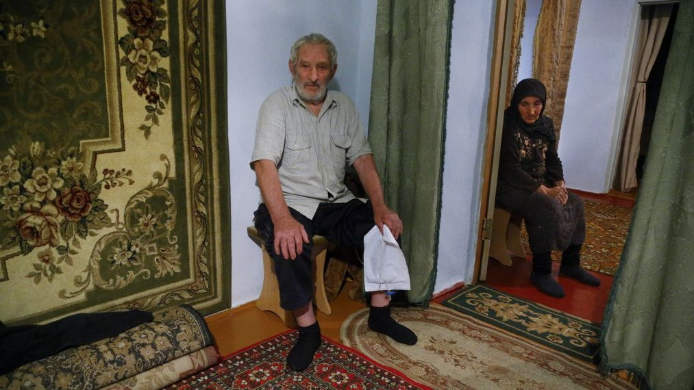 In this photo taken Thursday, Nov. 12, 2015, Zaynudin Magomedov with his wife, father of Rashid Magomedov who left to become an Islamic State fighter and was killed in Syria, speaks at home in the village of Komsomolskoye, Dagestan, Russia. (Sergei Grits/AP)