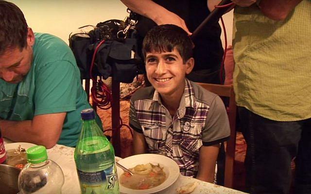Muhammad Ziad Sabateen eats dinner at the home of then Tekoa chief rabbi Menachem Froman about three years ago. (Screen capture)