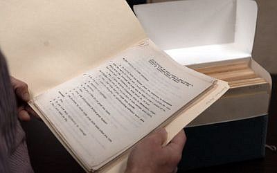 In this Wednesday, Nov. 11, 2015, photo, library archivist Tom White shows a folder containing some of the original transcripts from the Nuremburg trials in the archives at Duquesne University in Pittsburgh. (AP Photo/Keith Srakocic)