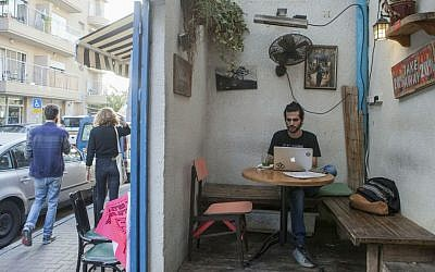 In this photo taken on Tuesday, Nov. 10, 2015, an Israeli man appears in a cafe in the Florentin neighborhood of Tel Aviv, Israel. (AP Photo/Dan Balilty)