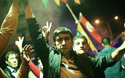 Youths use a flare as they celebrate preliminary election results of the pro-Kurdish Peoples's Democratic Party (HDP) in Diyarbakir, in Turkey's predominantly Kurdish southeast, late Sunday, Nov. 1, 2015 (AP Photo/Lefteris Pitarakis)