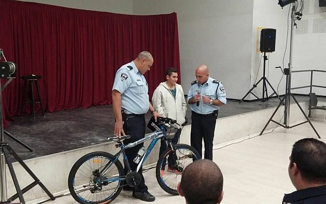13-year-old Naor, hurt in a October 12 stabbing attack in Pisgat Zeev, receives a new bicycle from police on November 9, 2015 (Facebook photo)