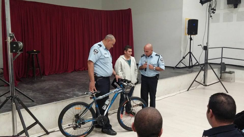 Naor Ben-Ezra, hurt in a October 12 stabbing attack in Pisgat Zeev, receives a new bicycle from police on November 9, 2015 (Facebook photo)