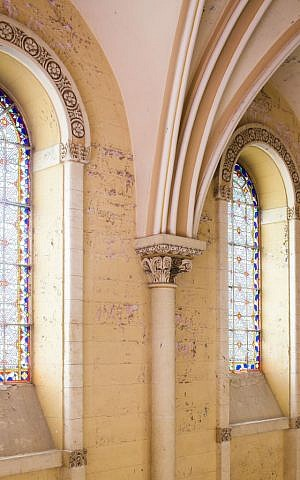 The stained glass windows and thickly painted walls of the former hospital, before restoration (Courtesy Amit Geron)