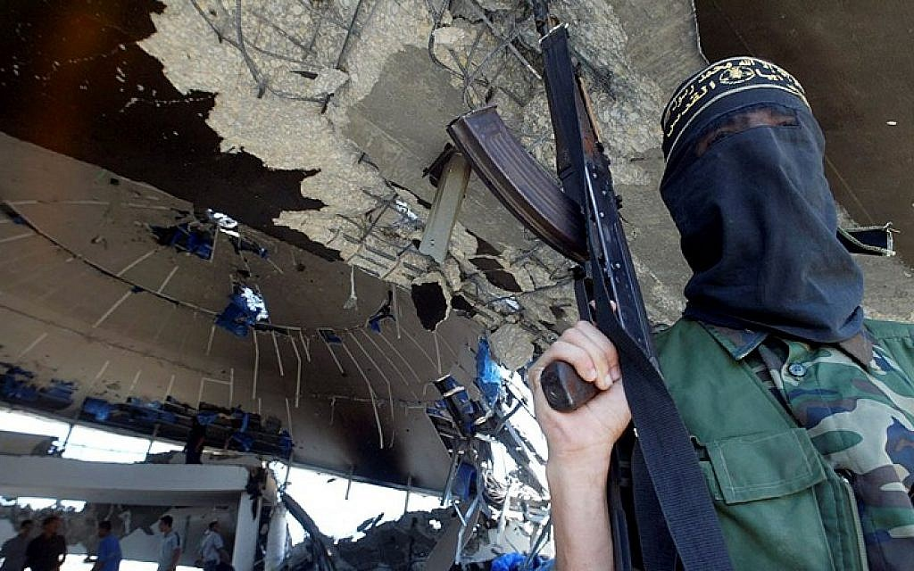Illustrative image of an armed member of the Islamic Jihad Movement standing inside the ruins of the Netzarim synagogue on September 12, 2005. (Ahmad Khateib /Flash90)