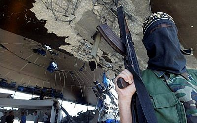 An armed member of the Islamic Jihad Movement stands inside the ruins of the Netzarim synagogue on September 12, 2005. (Ahmad Khateib /Flash90)