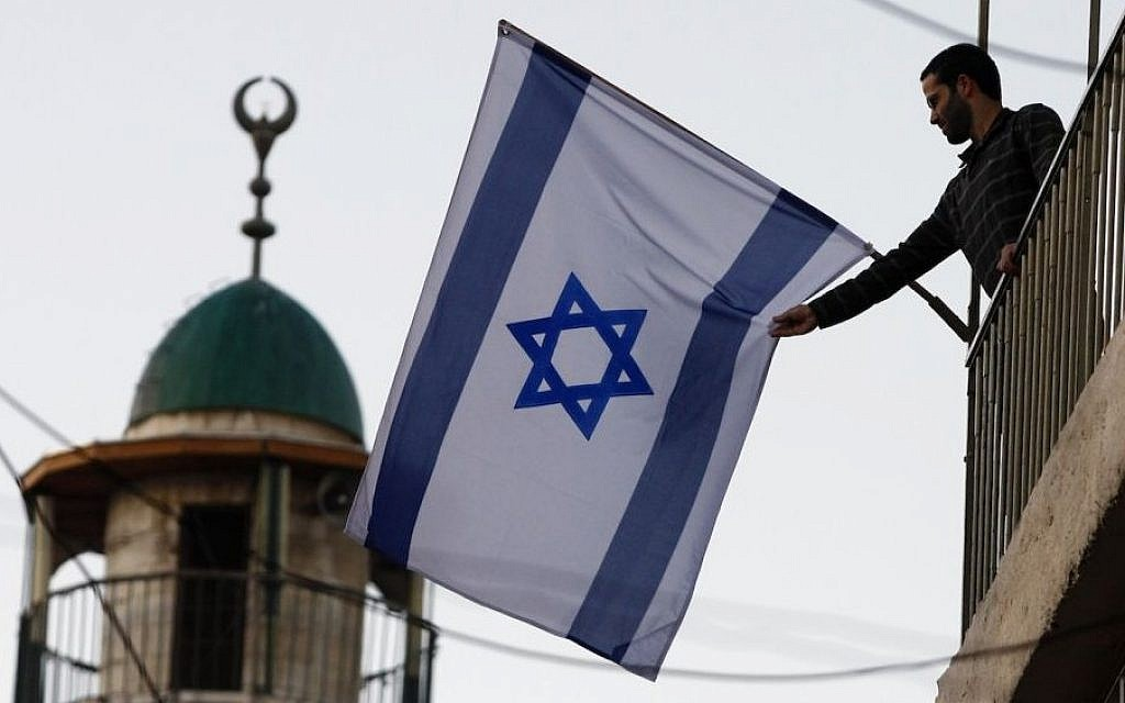 A Jewish-Israeli raising the flag of Israel near the Old City of Jerusalem. The number of Jewish residents in the Old City and predominantly Arab areas nearby has increased 40 percent since 2009. (Abir Sultan/Flash 90)