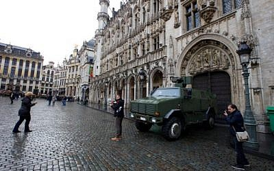 People posing for photos in front of a military vehicle next to the Grande Place square in central Brussels, November 21, 2015. (AFP/BELGA/Nicolas Maeterlinck)
