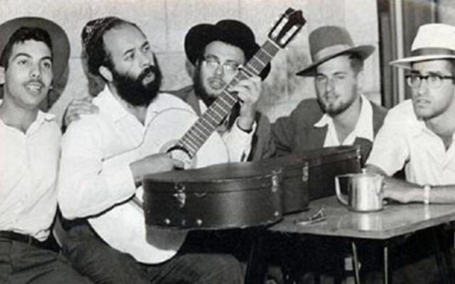 A young Rabbi Shlomo Carlebach playing guitar. (YouTube screenshot)