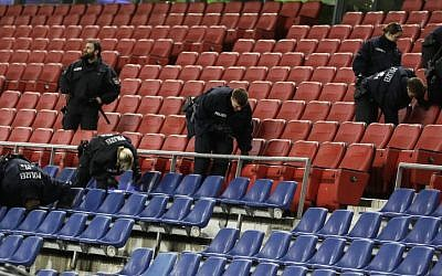 German police officers search between the seats of the stadium prior to an international friendly soccer match between Germany and the Netherlands in Hannover, Germany, November 17, 2015 (Markus Schreiber | The Associated Press)