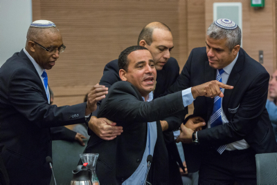 """Israeli parliament member Yoel Hasson is escorted out from a debate regarding the Israeli Jewish anti-assimilation """"Lehava"""" organization at the Internal Affairs Committee meeting in the Knesset on November 10, 2015. (Yonatan Sindel/FLASH90 )"""