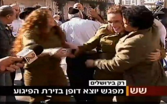 Umm al-Fahm woman Hawala Jaber (right) hugs and kisses a female IDF soldier a short time after a terror attack in Jerusalem on November 23, 2015. Jaber was earlier interviewed by Channel 2 and criticized the recent wave of Palestinian terror attacks. (screen capture: Channel 2)