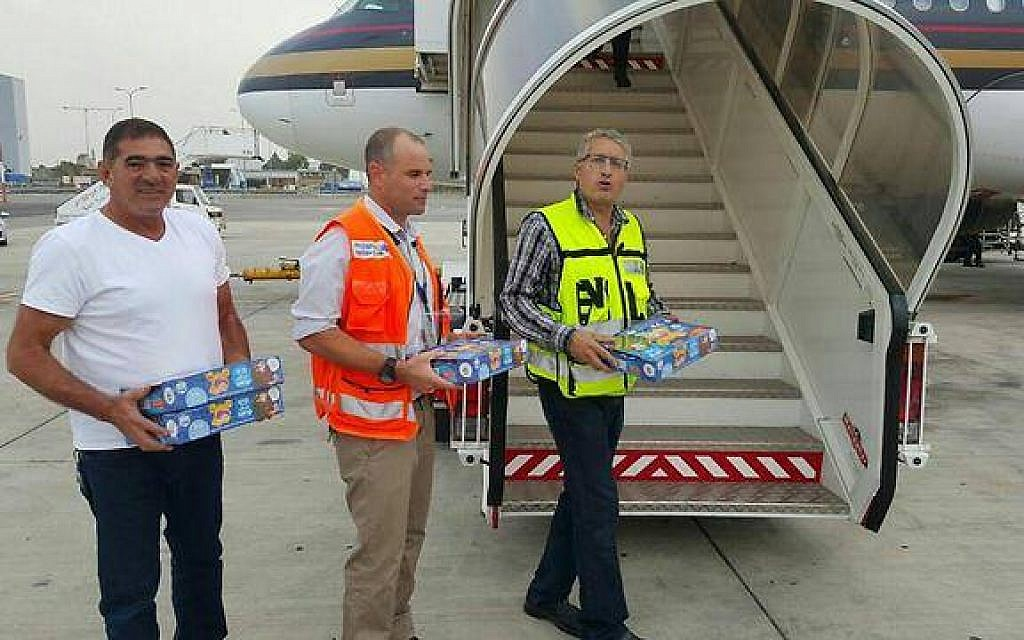 Ben Gurion Airport staff hold Israeli candies as they greet a Jordanian plane from Dubai that made an emergency landing in Tel Aviv on November 3, 2015 (photo credit: Israel Airports Authority)