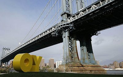 A bright yellow monumental sculpture by artist Deborah Kass sitting below the Manhattan Bridge in New York City November 11, 2015 (Kathy Willens/AP)