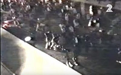A screen capture from an amateur video showing bodyguards and police jumping on Yitzhak Rabin assassin Yigal Amir in Tel Aviv on November 4, 1995. (screen capture: via YouTube)