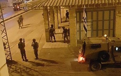 This image posted by Palestinian social media users overnight Saturday purports to show IDF soldiers outside the offices of a Hebron radio station in November, 2015. (screen capture: Facebook)
