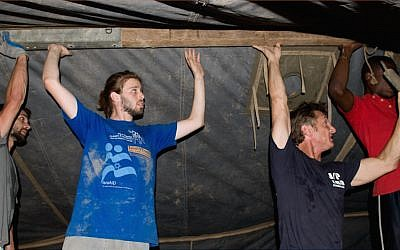 Actor Sean Penn in black t-shirt helping Tevel b'Tzedek volunteers following the earthquake in Haiti, 2010 (photo courtesy Tevel b'Tzedek)