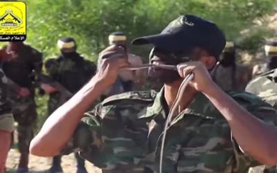 A Fatah fighter bites and chews on a snake in a terror promotion video posted on the organization's Facebook page in November 2015. (Screen capture from YouTube)