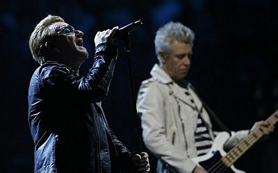 U2 singer Bono performs alongside bass player Adam Clayton on stage at the Bercy Accordhotels Arena in Paris, December 6, 2015.  (Photo by AFP/Thomas Samson)