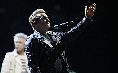 U2 singer Bono speaks to the audience at the Bercy Accordhotels Arena in Paris, December 6, 2015. (Photo by AFP/Thomas Samson)