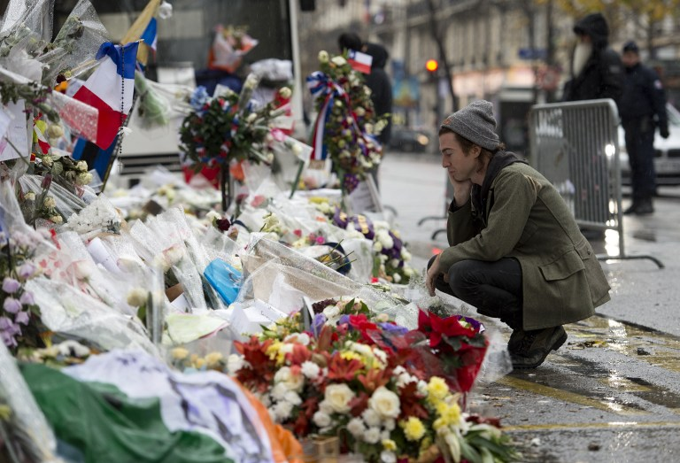Drummer of the US rock group Eagles of Death metal Julian Dorio pays tribute to the victims of the November 13 Paris terrorist attacks at a makeshift memorial in front of the Bataclan concert hall in Paris on December 8, 2015. The band returned to the venue, nearly a month after they survived a terror attack there in which 90 people died. (Miguel Medina/AFP)