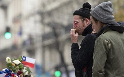 Singer of the US rock group Eagles of Death metal Jesse Hughes (L) and drummer Julian Dorio pay tribute to the victims of the November 13 Paris terrorist attacks at a makeshift memorial in front of the Bataclan concert hall in Paris on December 8, 2015.  (Miguel Medina/AFP)
