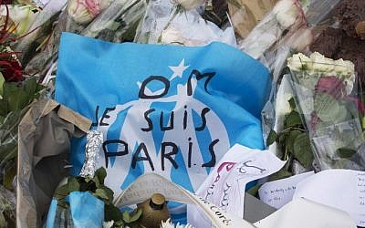 A picture taken on December 10, 2015 shows a flag of Marseille with the lettering 'I am Paris' (Je suis Paris) at a makeshift memorial  in front of the Bataclan concert hall in Paris in tribute to the victims of November 13, 2015 terror attacks. (AFP / JOEL SAGET)