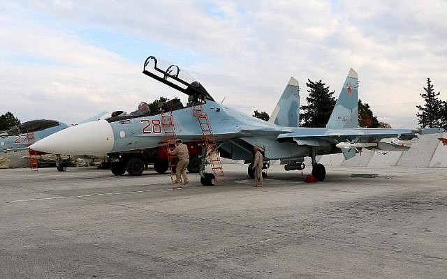 Russian servicemen prepare a Russian Sukhoi Su-30SM fighter jet before a departure for a mission at the Russian Hmeimim military base in Latakia province, Syria, on December 16, 2015. (AFP/Paul Gypteau)