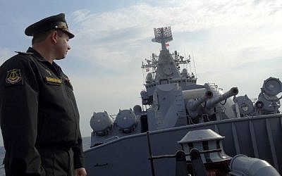 Russian Navy Captain Alexander Shvarts stands in front of an artillery system on the Russian missile cruiser Moskva as it patrols in the Mediterranean Sea, off the coast of Syria, on December 17, 2015. (Max Delany/AFP)